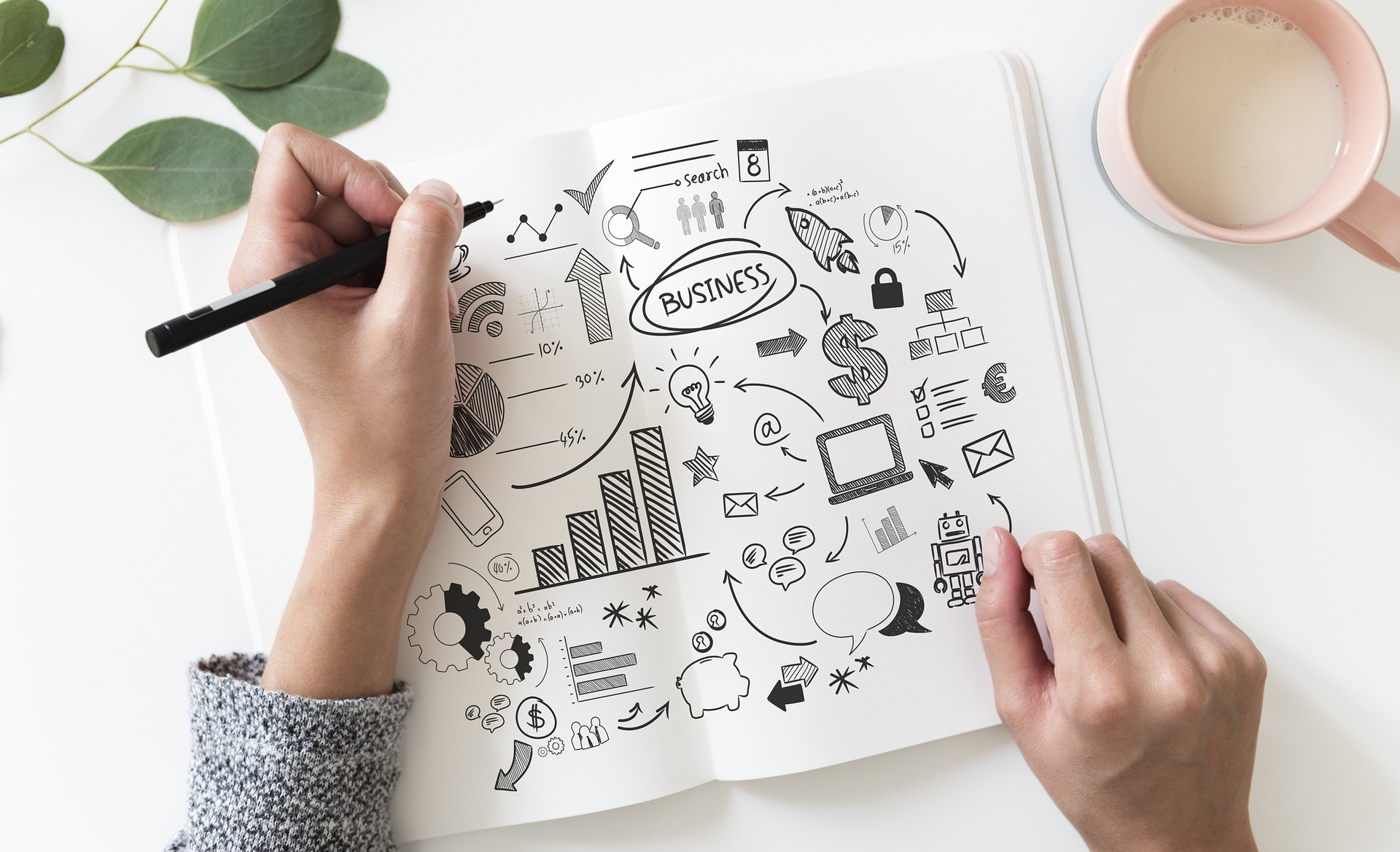 a woman doodling in a pad on business topics to come up with a design for a portfolio