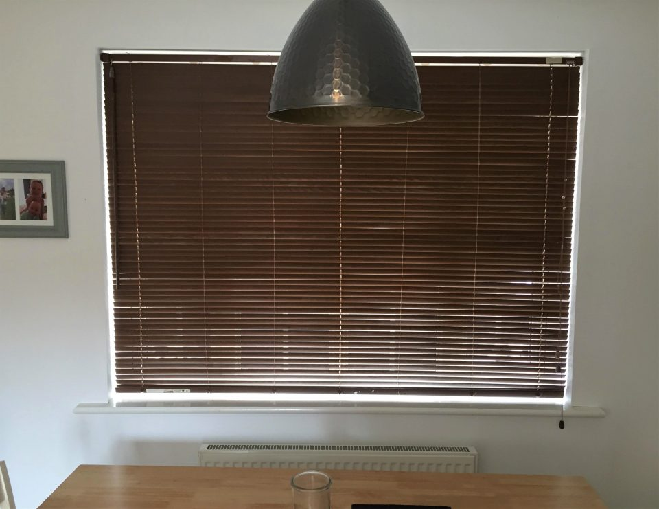 a dark brown venetian blind in a window in a kitchen