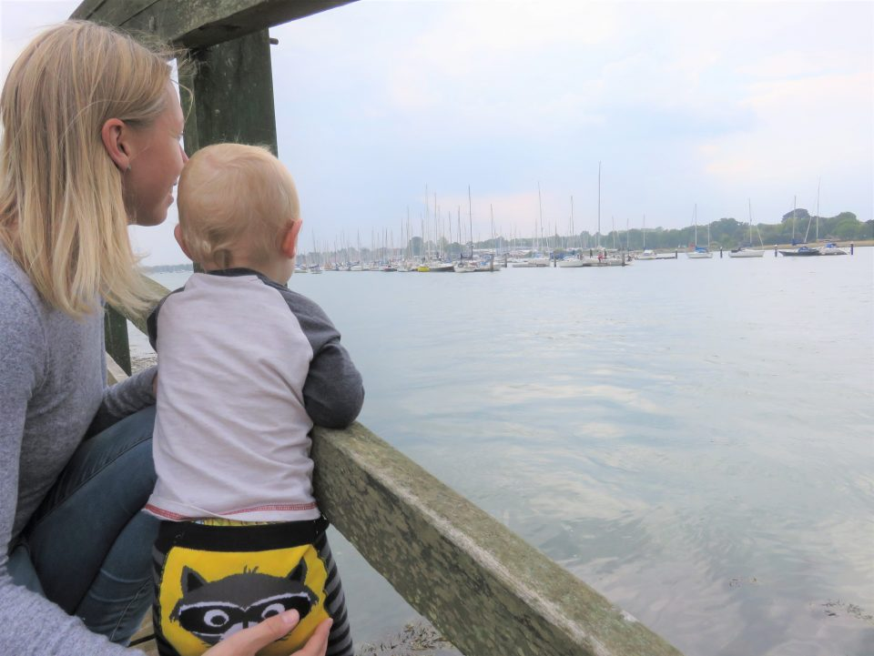 Mum and baby on a bridge looking over at boats