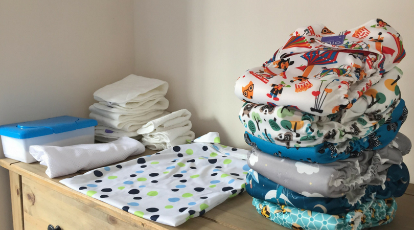 pile of cloth nappies a wetbag and wipes