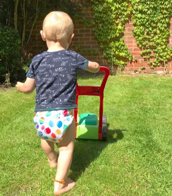 william pretending to mow the lawn in his easyfit reusable nappy