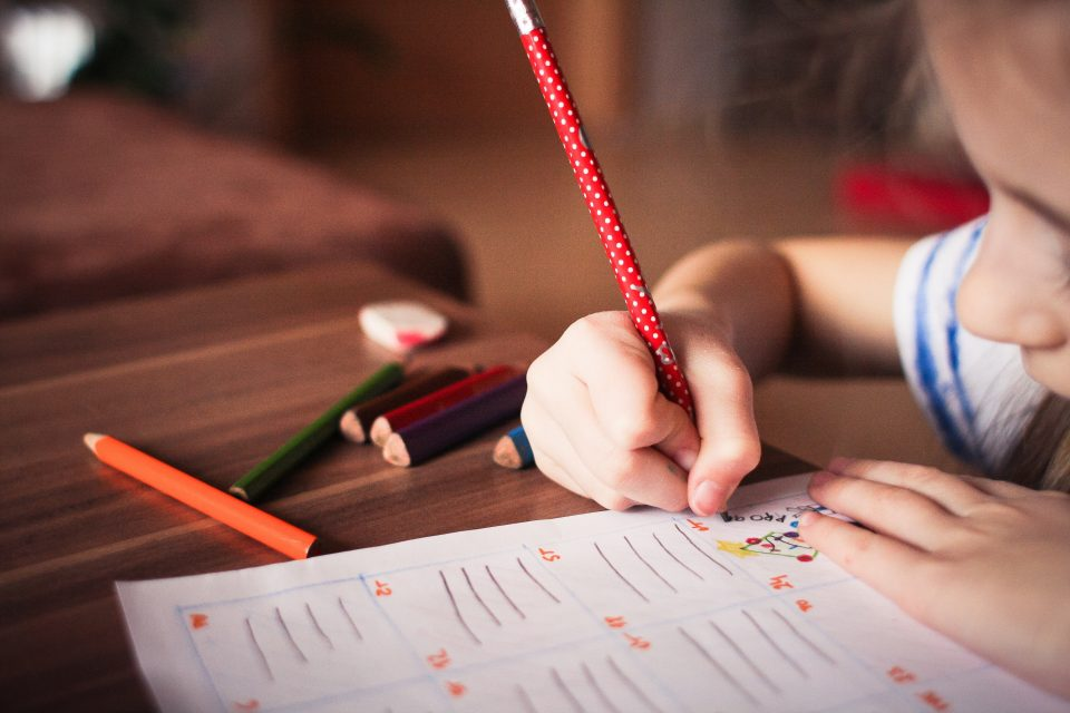 child holding a pen and writing