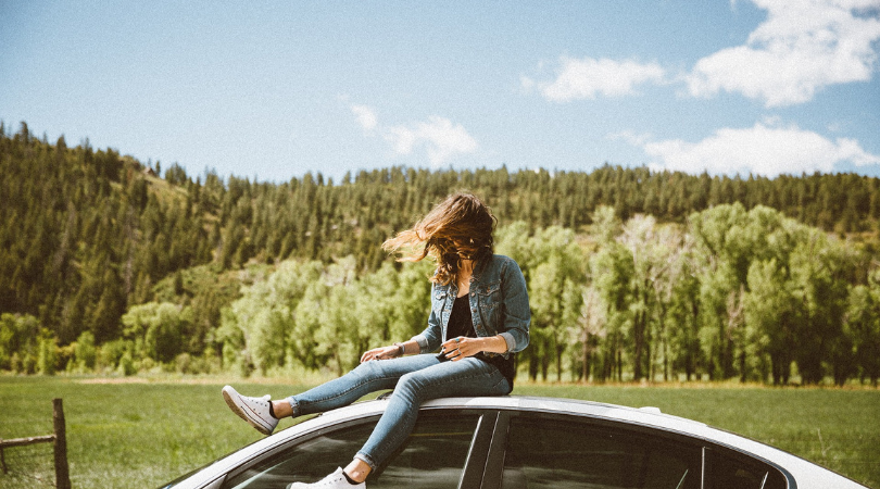 woman sat on car with trees behind her