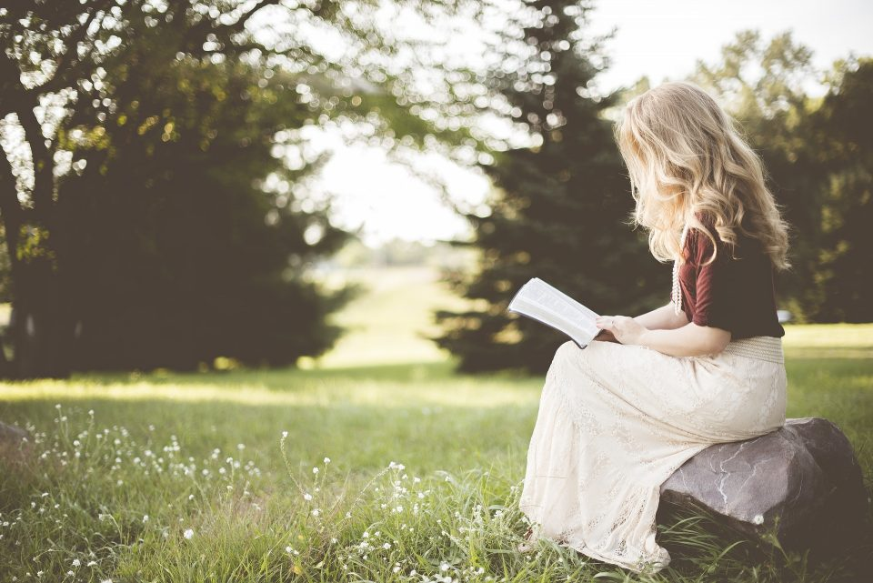 lady on a rock reading a book looks like she is having down time