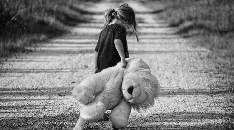 little girl holding a large lion toy