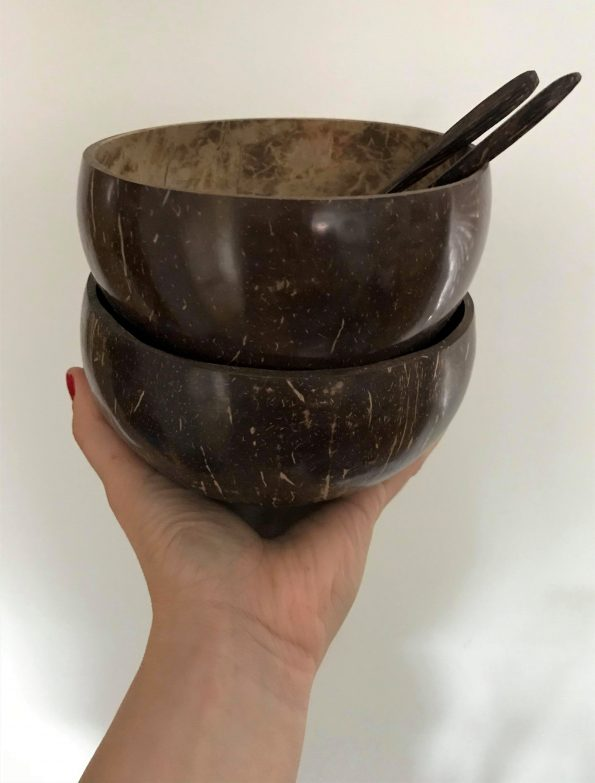 hand holding up 2 coconut bowls and spoons