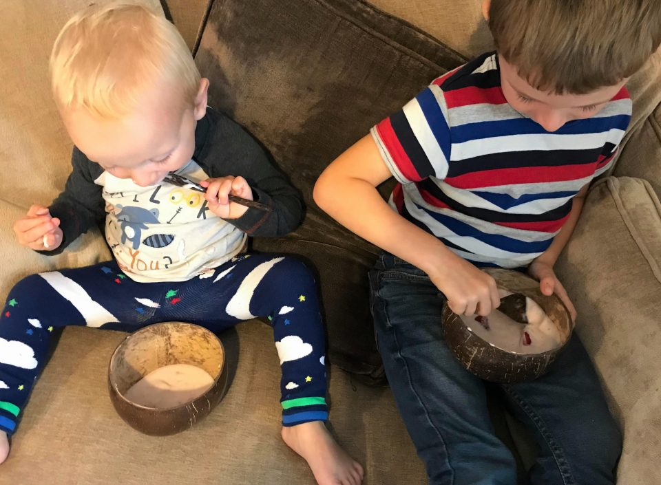 Jake and William eating the yoghurt from the coconut bowls
