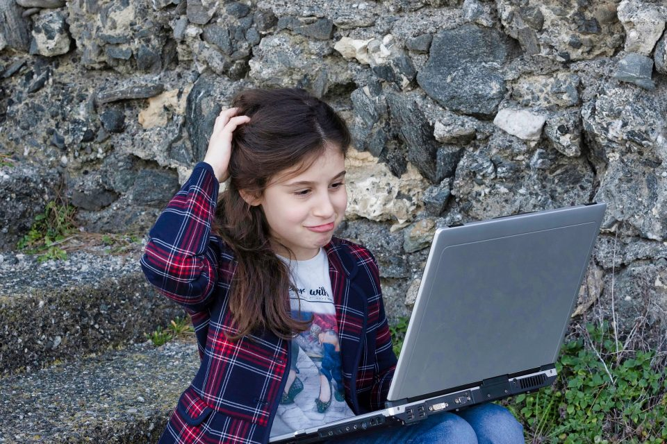 girl on laptop scratching her head