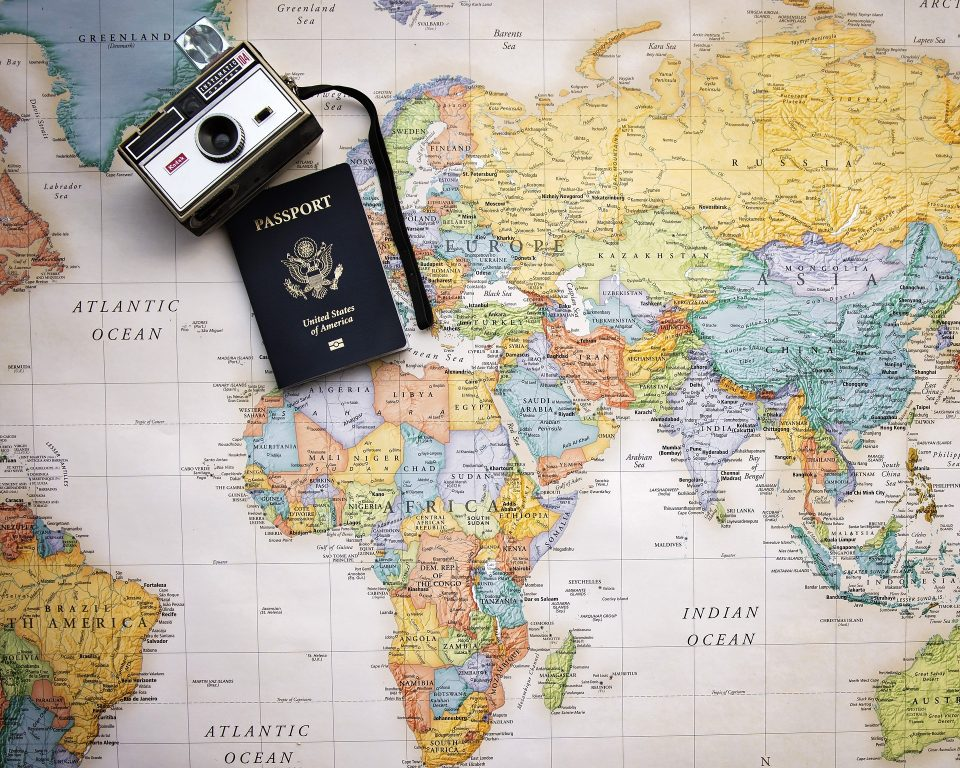 map of the world, camera and passport