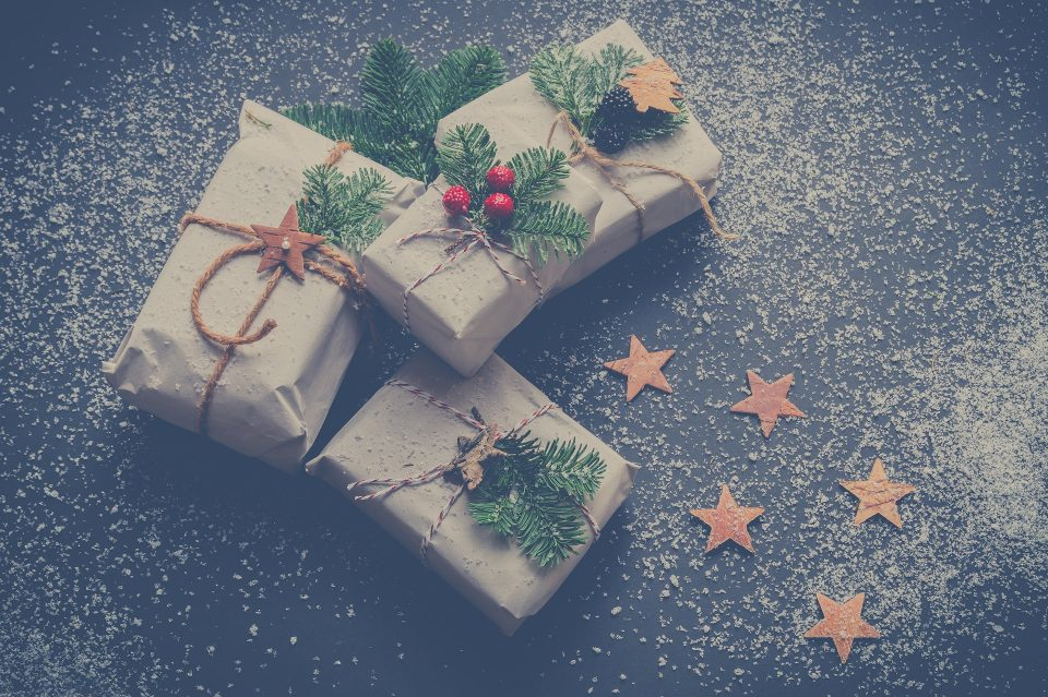 eco-friendly Christmas presents wrapped in brown paper and string with holly as decoration