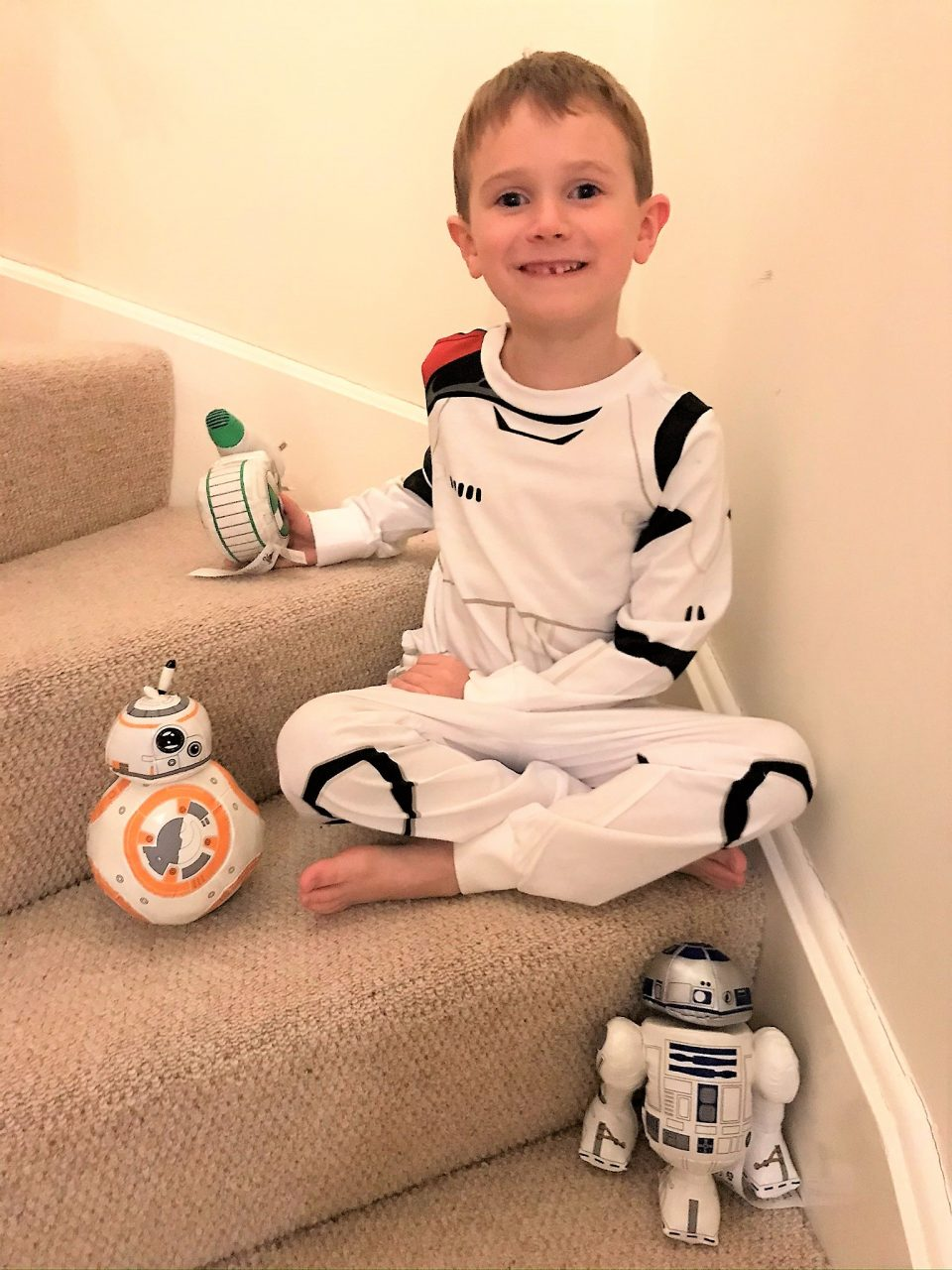 Jake sat on the stairs with his shopDisney products