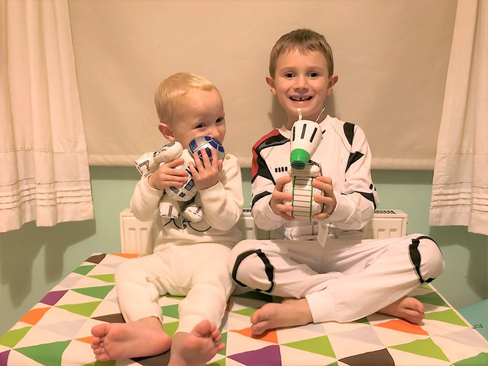 Jake and william sat on a toybox in their shopDisney outifts holding the star wars toys