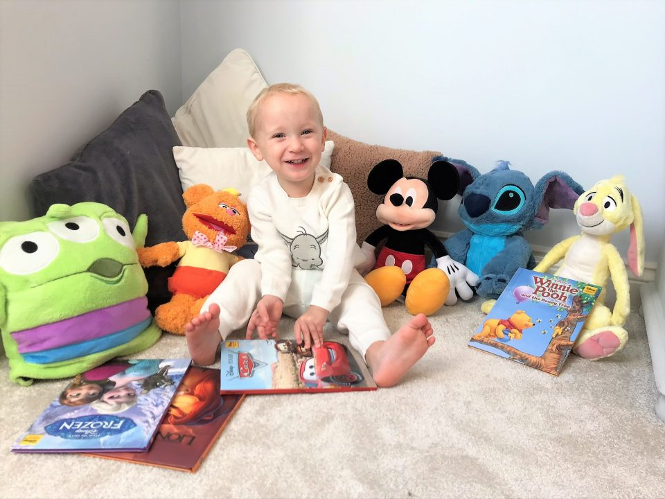 William smiling whilst holding a Disney book