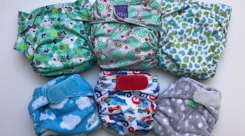 a mixture of popper and velcro cloth nappies on a white background