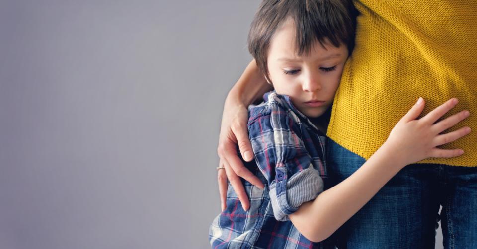 a small boy hugging a lady