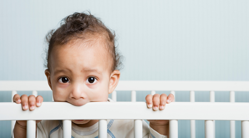 baby teething chewing the side of the cot
