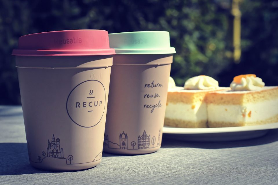 reusable coffee cups next to a cake for a more sustainable choice