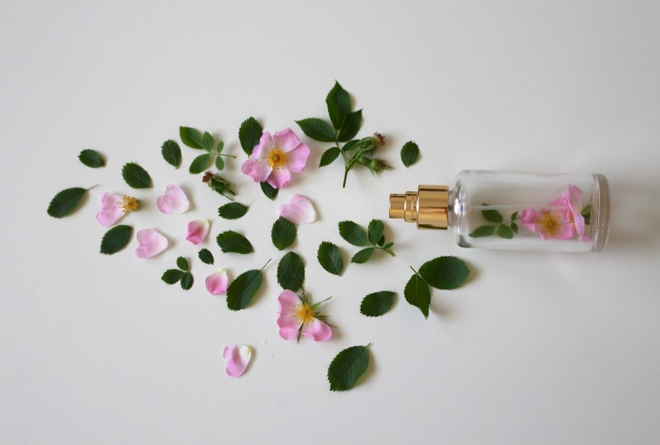 spray water bottle with flowers laid around it on a white background