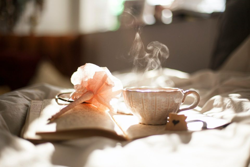 cup of tea on a bed with a book and flower to show that reading can be a positive new year's resolution