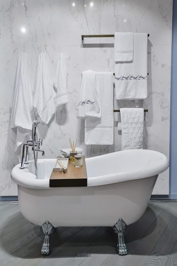 bathroom with towels hanging on a rail and hook behind