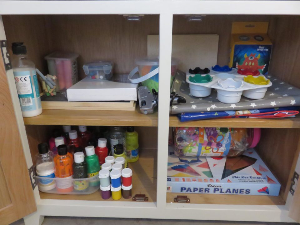 inside the arts cupboard which has paints, chalk boards, chalk etc