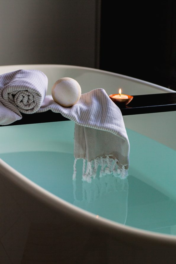 bath of water with towels and a candle