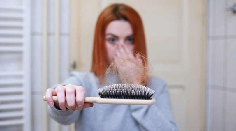 lady holding out a brush with hair on it