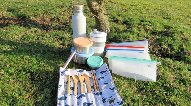 the on the go eco products laying on the grass under a tree