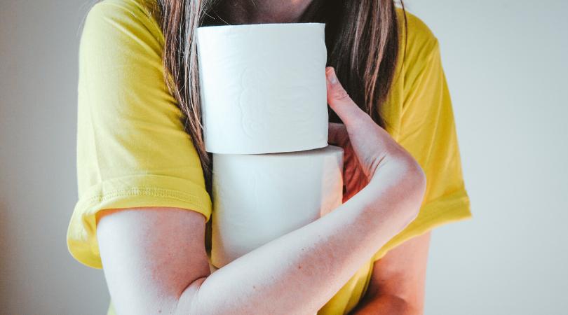 a woman hugging toilet rolls