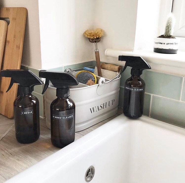 3 bottles of homemade cleaners sat on a sink