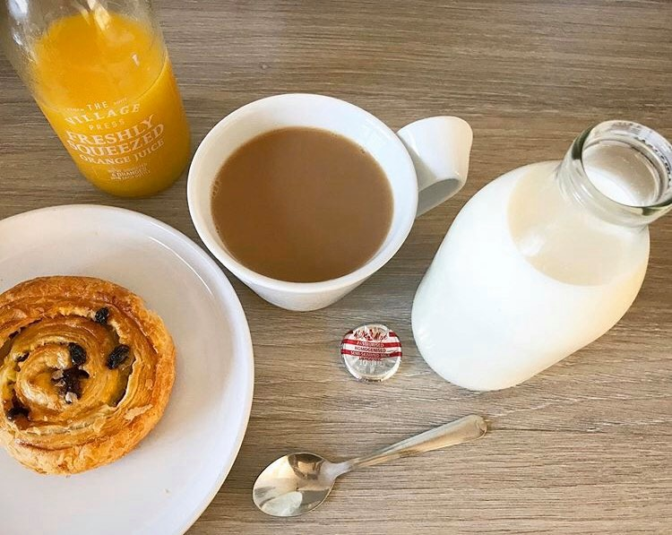 a cup of tea, pastry, milk and orange in glass bottles
