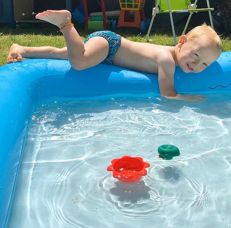 william laying on the side of the paddling pool in his reusable swim nappy