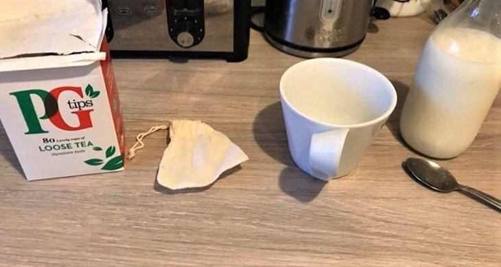 reusable tea bag next to a cup, the loose tea from Pg tips and a bottle of milk