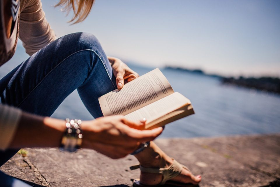 a lady reading a book by the sea