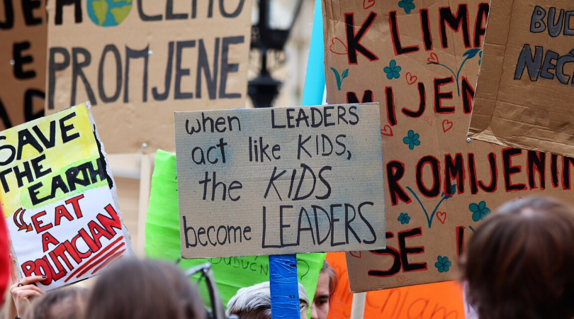 a sign being held up that states when leaders act like kids, the kids become the leaders