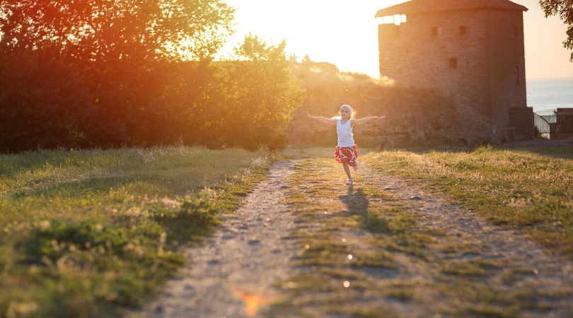 a child dancing around outside in the summer sun