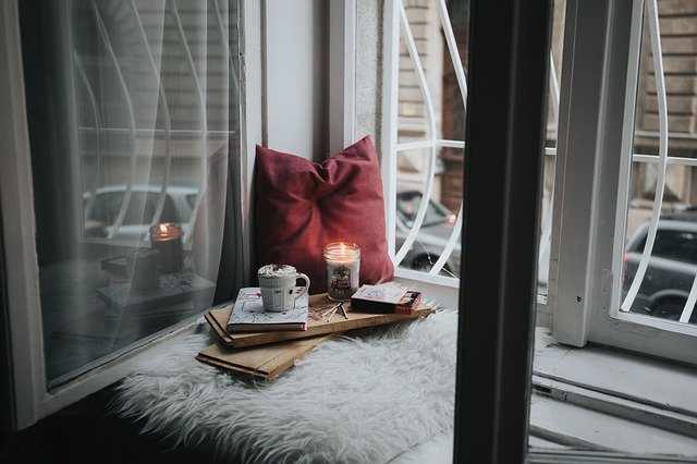 a window seat with a tray with a drink and candle on it