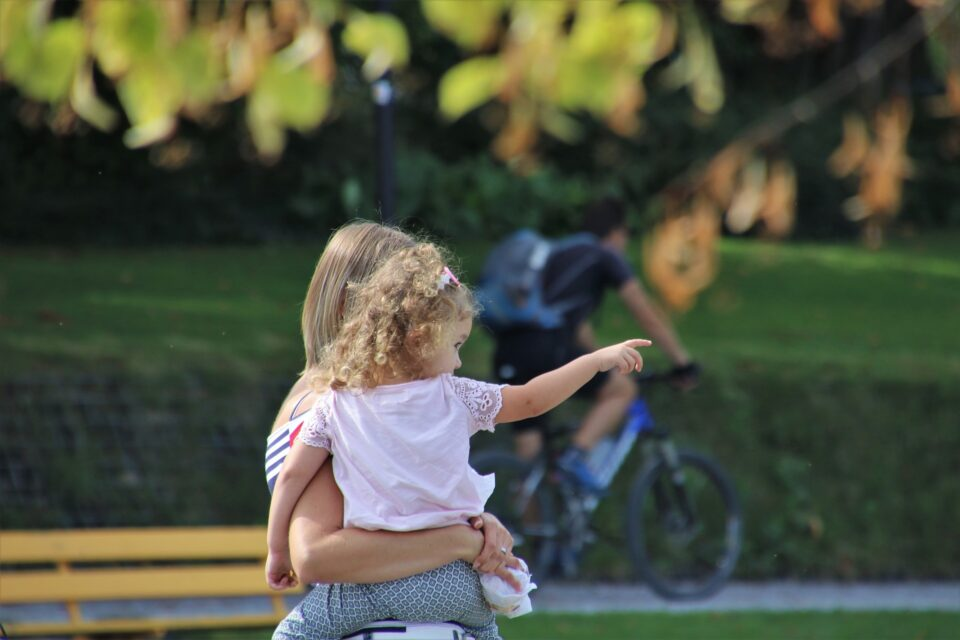 mum holding a girl in a park