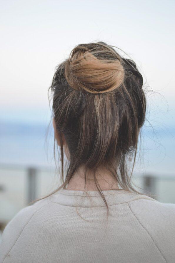 a messy bun on mousy brown hair