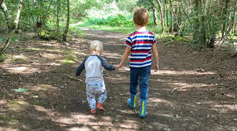 jake and William walking through a woods holding hands