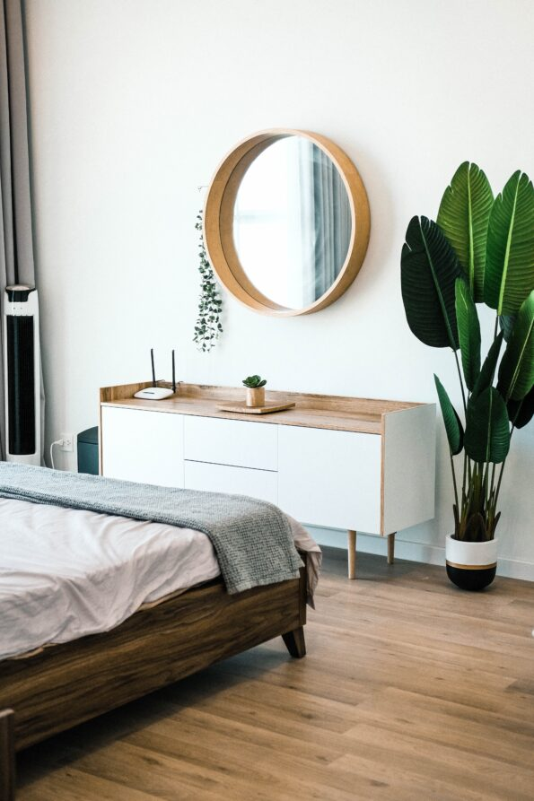 abedroom with a bed, dressing table, mirror and plant