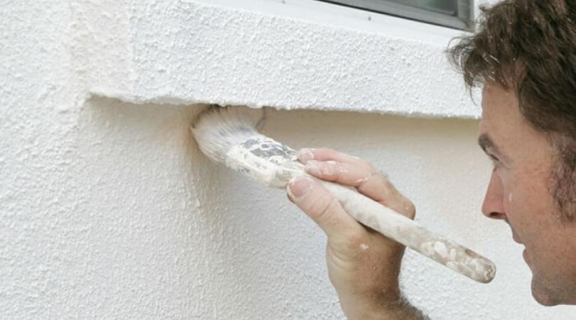 a man painting an exterior wall