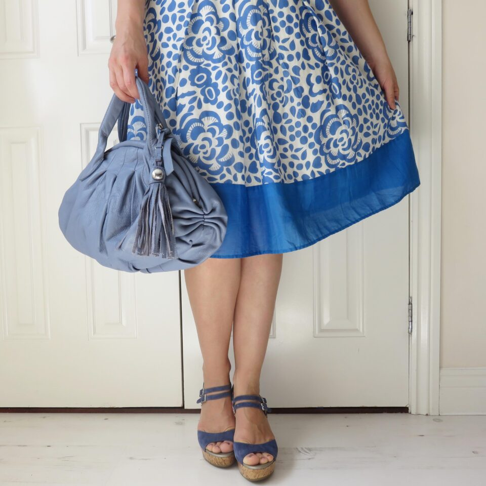 me wearing a blue flowery skirt with blue wedges and a blue handbag