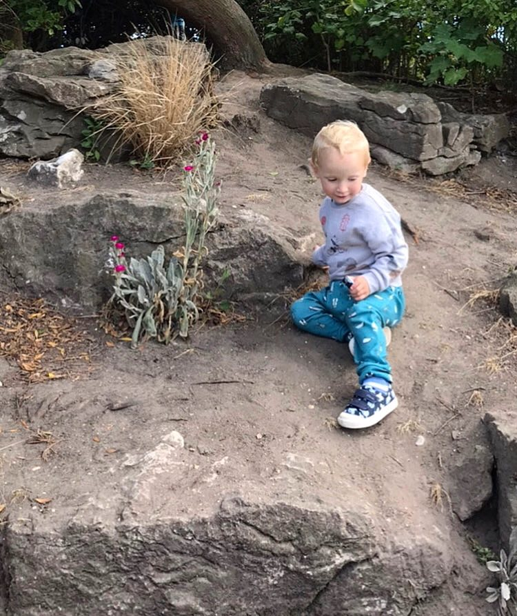 William wearing soft trousers and a jumper sitting on an earthy bank