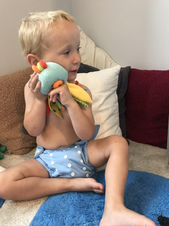 William cuddling a soft toy wearing his hippynut nappy