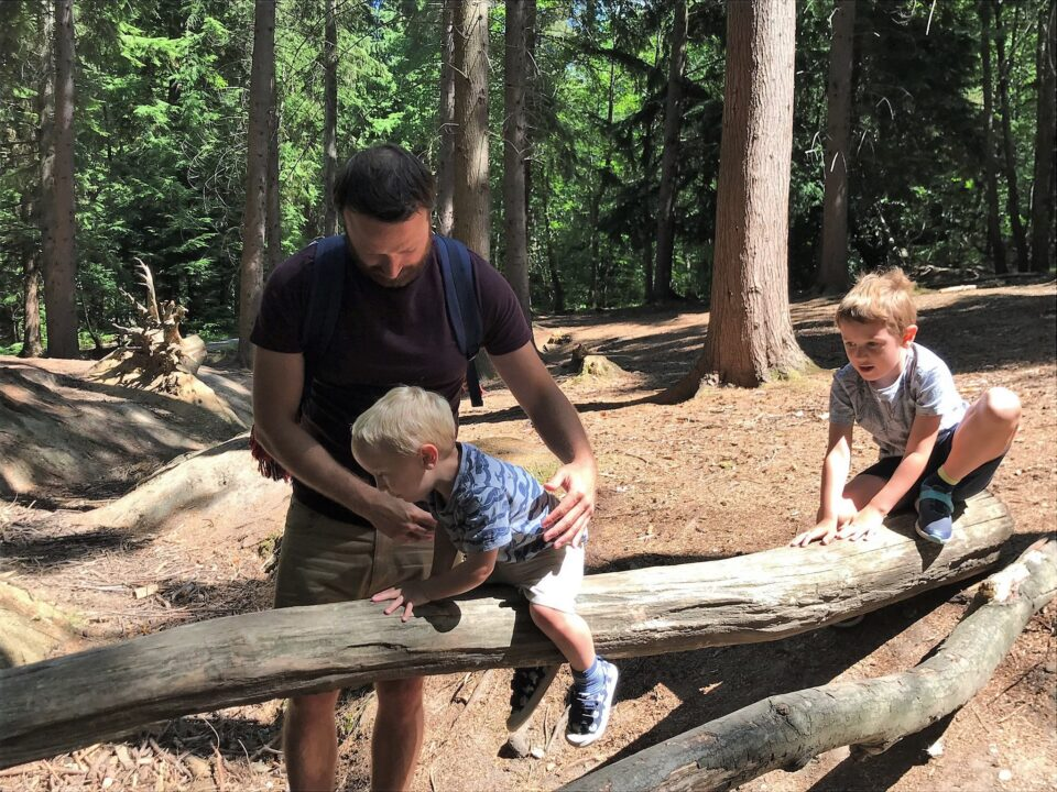 Dad helping two kids across a log in the forest