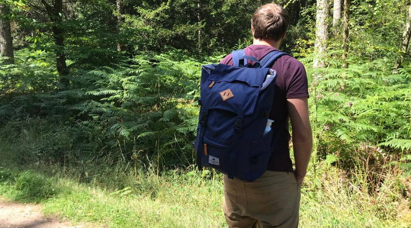 man wearing the lazy bear lance navy backpack in the forest