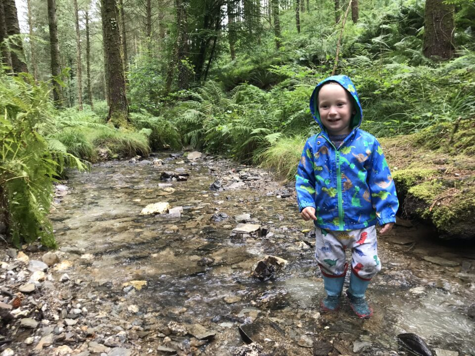 toddler in a river wearing wellies and a waterproof jacket
