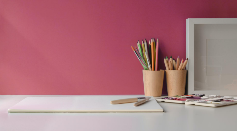 pencils, paper and a white frame on a white worktop with a purple feature wall