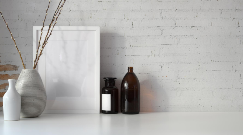 glass bottles, picture frame, vases on a white worktop